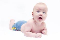 Baby, das in den blauen Hosen liegt Lizenzfreie Stockfotografie