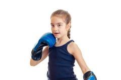 Baby, das in den Boxhandschuhen und in den Blicken in Richtung zu lokalisiert auf einem weißen Hintergrund steht Lizenzfreie Stockfotografie