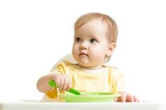 Baby, das den Jogurt oder Püree lokalisiert auf weißem Hintergrund isst Stockfotos