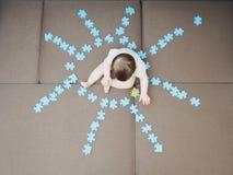 Baby, das in den mittleren Puzzlespielstücken zu Hause gefaltet als Form der Sonne auf Wohnzimmer des Sofas sitzt Stockfoto