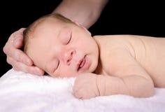 Baby, das in der Hand des Vatis schläft Stockbild