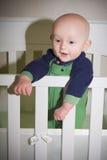 Baby, das in der Krippe steht Lizenzfreies Stockfoto