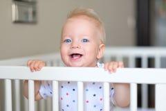 Baby, das in der Krippe steht Lizenzfreie Stockfotografie