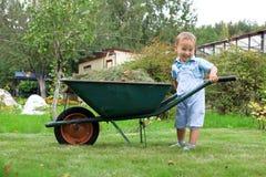 Baby, das eine Schubkarre im Garten drückt Lizenzfreie Stockfotografie