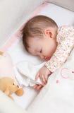Baby, das in einem Feldbett mit Friedensstifter und Spielzeug schläft Stockfotografie