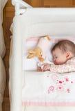 Baby, das in einem Feldbett mit Friedensstifter und Spielzeug schläft Lizenzfreies Stockbild