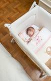 Baby, das in einem Feldbett mit Friedensstifter und Spielzeug schläft Lizenzfreie Stockfotografie