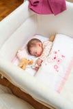 Baby, das in einem Feldbett mit Friedensstifter und Spielzeug schläft Stockbild
