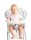 Baby, das in einem Hochstuhl lokalisiert sitzt Stockbild