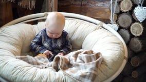 Baby, das in einem Stuhl spielt im Telefon sitzt stock footage