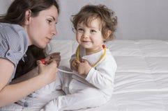 Baby, das einen Doktor mit Mutter spielt stockbilder