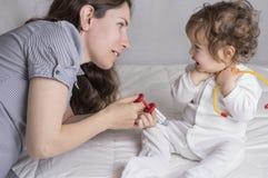 Baby, das einen Doktor mit Mutter spielt lizenzfreies stockbild