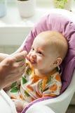 Baby, das erste feste Nahrung von einem Löffel mit g isst Stockbild