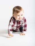 Baby, das in Flanell und in Jeans in Richtung zur Kamera kriecht stockbild