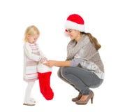 Baby, das Geschenk von der Weihnachtssocke herausnimmt Lizenzfreie Stockbilder
