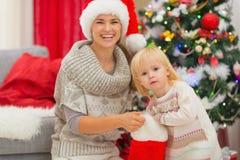 Baby, das Geschenk von der Weihnachtssocke herausnimmt Lizenzfreies Stockbild