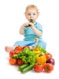 Baby, das gesundes Nahrungsmittelgemüse auf Weiß isst Stockbild