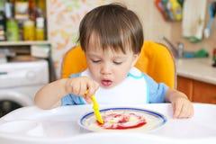 Baby, das Grießbrei mit Stau isst Lizenzfreie Stockbilder