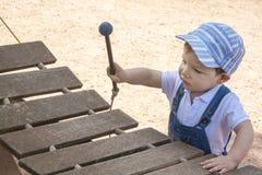 Baby, das hölzernes Xylophon am Spielplatz spielt lizenzfreie stockfotos