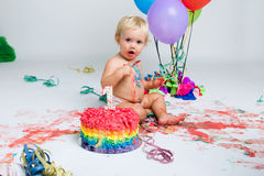 Baby, das ihr erstes bithday mit feinschmeckerischem Kuchen feiert Lizenzfreie Stockfotos