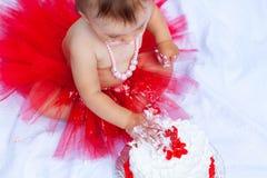 Baby, das ihren ersten Geburtstagskuchen isst Stockfotos