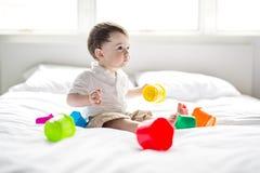 Baby, das im Bett auf weißer Decke liegt Netter Junge, der mit Würfeln spielt Lizenzfreie Stockfotografie