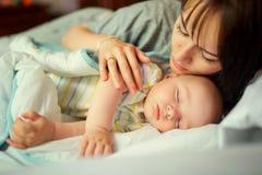Baby, das im Bett mit Mutter schläft obacht stockfotos