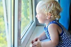 Baby, das im Fenster schaut Stockbild