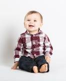 Baby, das im Flanell und in Jeans schauen über Kamera sitzt lizenzfreie stockfotografie