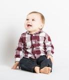 Baby, das im Flanell und in Jeans schauen linkes Lachen sitzt stockfotografie