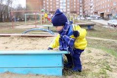 Baby, das im Frühjahr mit Sand auf Spielplatz spielt Lizenzfreies Stockfoto