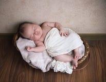 Baby, das im Korb auf dem Bretterboden schläft Lizenzfreie Stockfotos