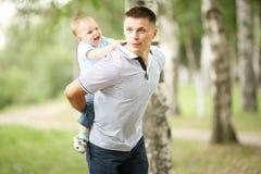Baby, das im Park mit Vati spielt Lizenzfreie Stockbilder