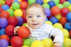 Baby, das im Spielplatzballpool spielt Lizenzfreies Stockfoto