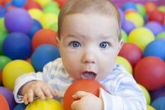 Baby, das im Spielplatzballpool spielt Stockbild
