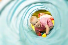 Baby, das innerhalb eines Spielzeugtunnels spielt Stockbilder