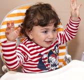 Baby, das Kind in einem Stuhllachen der Kinder sitzt, freut sich Lizenzfreie Stockfotos