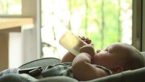 Baby, das Milch von der Flasche isst stock video