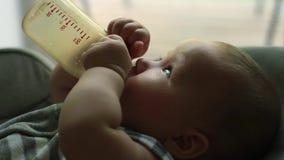 Baby, das Milch von der Flasche isst stock video footage