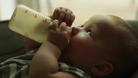 Baby, das Milch von der Flasche isst stock footage