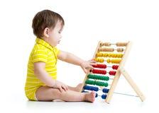 Baby, das mit Abakusspielzeug spielt Konzept von früh Stockfotografie