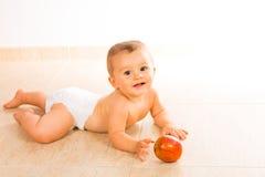 Baby, das mit Apfel spielt Lizenzfreie Stockfotografie