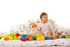 Baby, das mit Bällen im Bett spielt Stockfotos