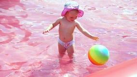 Baby, das mit Ball im Pool spielt stock footage