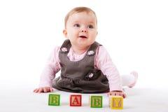 Baby, das mit Blöcken aufwirft Stockbild