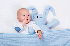 Baby, das mit Blau gestricktem Häschenspielzeug spielt Stockfotos