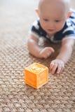 Baby, das mit Block auf gesponnener Wolldecke spielt lizenzfreie stockfotografie