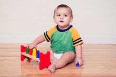 Baby, das mit buntem hölzernem Spielzeug spielt Stockbilder