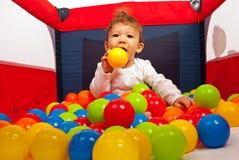 Baby, das mit bunten Bällen spielt Lizenzfreies Stockbild