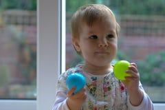 Baby, das mit dem farbigen Balllächeln spielt lizenzfreies stockbild